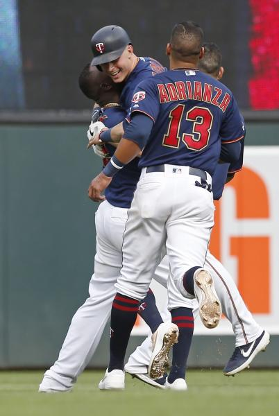 Minnesota Twins' Max Kepler, center, is swarmed by teammates celebrating his walk-off RBI single as the Twins beat the Oakland Athletics 7-6 in a baseball game Sunday, July 21, 2019, in Minneapolis. (AP Photo/Jim Mone)