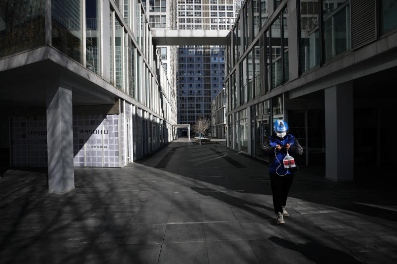 A food delivery worker passes a deserted compound of a commercial office building during the lunch break in Beijing, Monday, Feb. 17, 2020. Chinese authorities on Monday reported a slight upturn in new virus cases and hundred more deaths, as the military dispatched hundreds more medical workers and extra supplies to the city hit hardest by the 2-month-old outbreak. (AP Photo/Andy Wong)