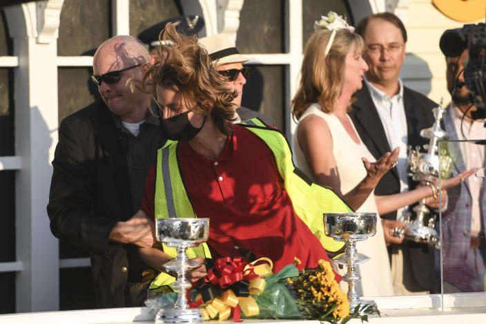 Security removes a protester, in red shirt, after he reached the stage during the trophy presentation after Flavien Prat atop Rombauer won the 146th Preakness Stakes horse race at Pimlico Race Course, Saturday, May 15, 2021, in Baltimore. (AP Photo/Will Newton)