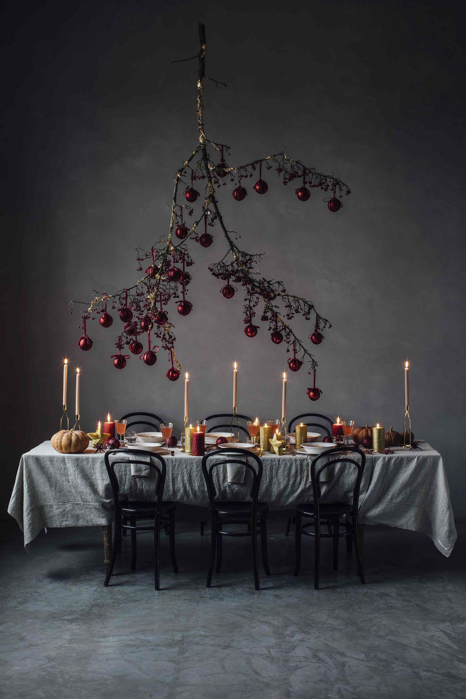 """<p>Steer away from the traditional tree and max up the wow factor with a bauble-dressed sprig suspended above the table, as inspired by Laura Muthesius and Nora Eisermann of blog Our Food Stories.</p><p>'Crystal <strong>baubles</strong>, £4.99 each; <strong>tableware</strong>, <strong>glassware</strong>; <strong>candles</strong>; and <strong>table linen</strong>, all from a selection, Zara Home (<u><a href=""""https://www.zarahome.com/gb/dining-c1089014.html"""" rel=""""nofollow noopener"""" target=""""_blank"""" data-ylk=""""slk:zarahome.com"""" class=""""link rapid-noclick-resp"""">zarahome.com</a></u>). For similar vintage 'Bentwood Bistro' <strong>chairs</strong>, try Vinterior (<u><a href=""""https://www.vinterior.co/"""" rel=""""nofollow noopener"""" target=""""_blank"""" data-ylk=""""slk:vinterior.co"""" class=""""link rapid-noclick-resp"""">vinterior.co</a></u>). <strong>Bough </strong>styled by Mary Lennox Flower Studio. (<u><a href=""""http://marylennox.de/"""" rel=""""nofollow noopener"""" target=""""_blank"""" data-ylk=""""slk:marylennox.de"""" class=""""link rapid-noclick-resp"""">marylennox.de</a></u>)</p>"""