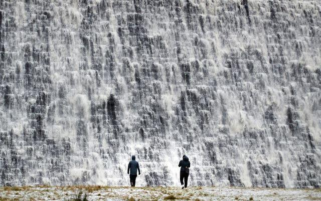 People watch as water cascades down Derwent Dam in the Peak District