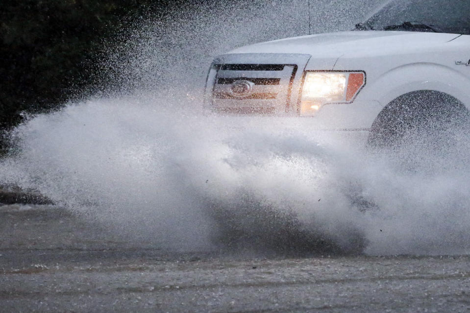 A vehicle travels along a flooded road as severe weather produces torrential rainfall, Tuesday, May 4, 2021 in Vestavia, Ala. (AP Photo/Butch Dill)