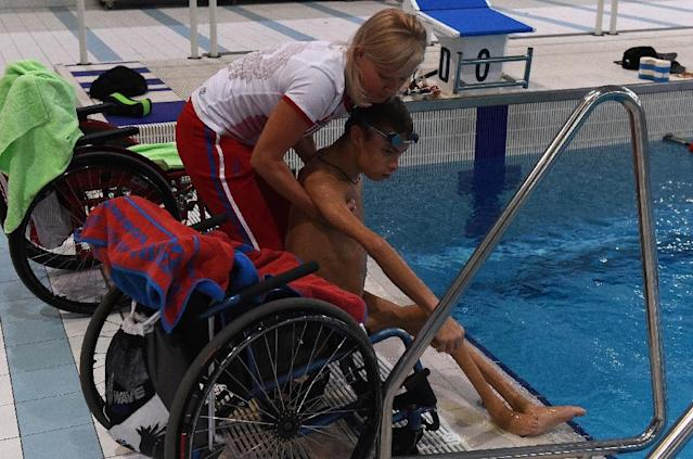 Coach Olesya Alexandrova helps paralympic swimmer Alexander Makarov after a training session in the town of Ruza on August 18, 2016 (AFP Photo/Vasily Maximov)