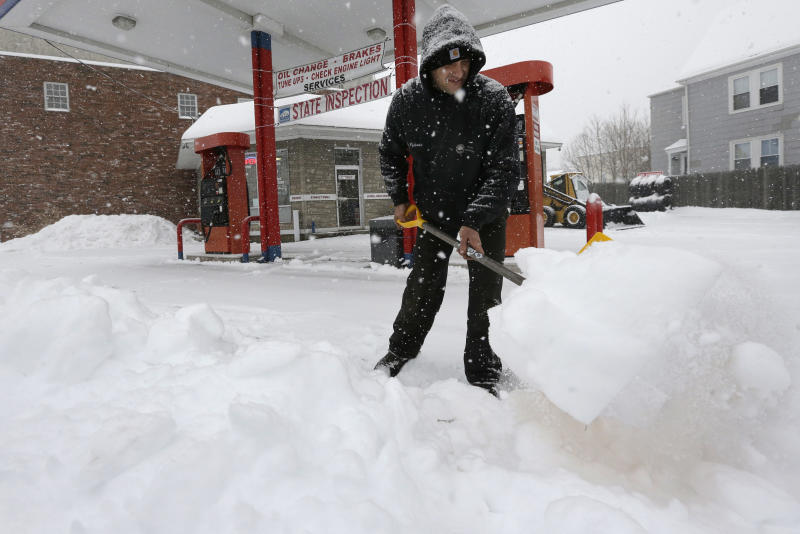 Andrew Pyliotis, of Wrentham, Mass., shovels snow in front of his gas station in Norwood, Mass., Wednesday, Feb. 5, 2014. Six to 12 inches of snow is expected around Boston, with 3 to 6 inches in southeastern areas before changing to sleet and rain. (AP Photo/Steven Senne)