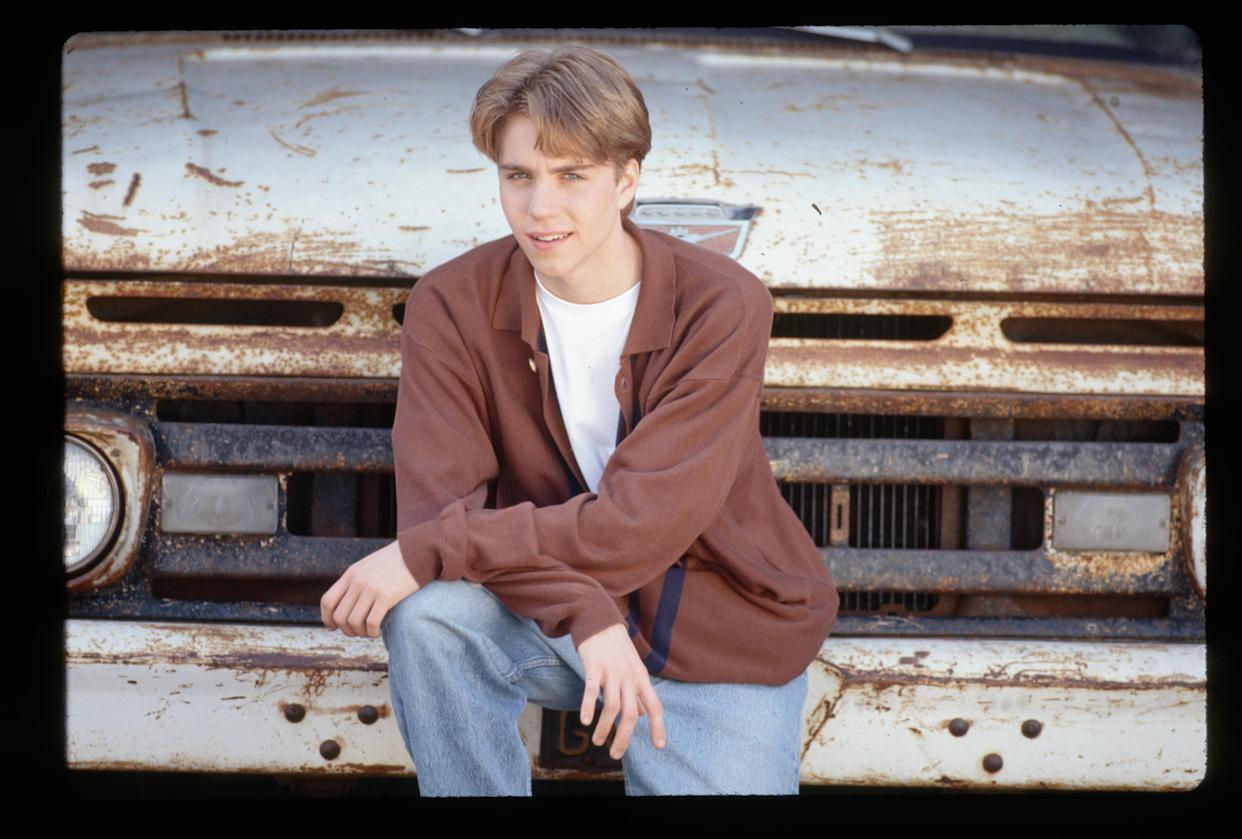 (Original Caption) : 1994-Actor Jonathan Brandis is shown leaning on the front bumper of a rusty old truck.   (Photo by Lynn Goldsmith/Corbis/VCG via Getty Images)