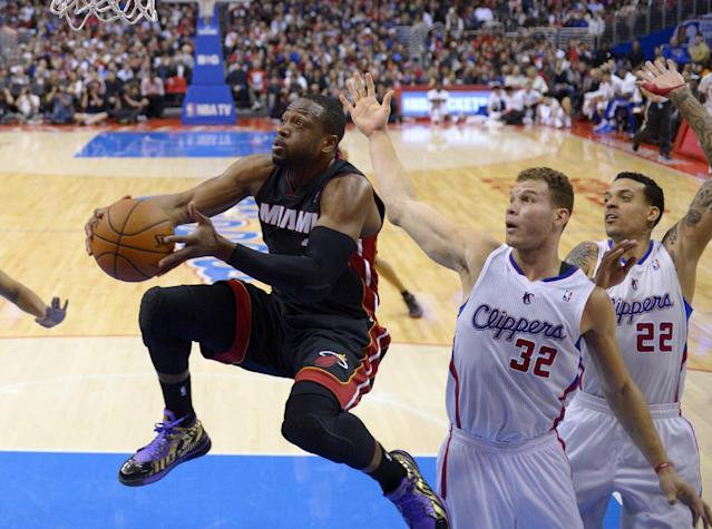 Miami Heat guard Dwyane Wade, left, goes up for a shot as Los Angeles Clippers forward Blake Griffin, center and forward Matt Barnes defend during the first half of an NBA basketball game, Wednesday, Feb. 5, 2014, in Los Angeles. (AP Photo/Mark J. Terrill)