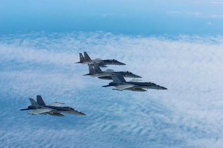 Japan's Self-Defense Force's F-15 fighter jets conduct an air exercise with U.S. Navy F/A 18 Hornet aircrafts in the skies above the Sea of Japan