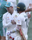 Australia's Joe Burns, right, is congratulated by his captain Tim Paine after Burns hit a 6 to win their match over India on the third day of their cricket test match at the Adelaide Oval in Adelaide, Australia, Saturday, Dec. 19, 2020. (AP Photo/David Mariuz)