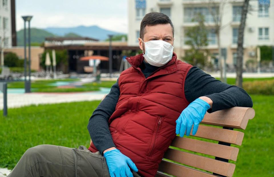 Man in a face mask sits on a bench and looks at the street