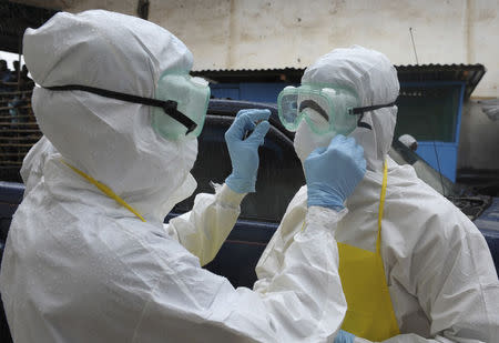 Health workers wearing protective clothing prepare themselves before to carrying an abandoned dead body presenting with Ebola symptoms at Duwala market in Monrovia