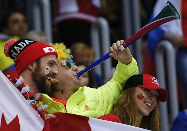Hockey fans cheer on Canada in the second period of a men's ice hockey game against Austria at the 2014 Winter Olympics, Friday, Feb. 14, 2014, in Sochi, Russia. (AP Photo/Mark Humphrey)