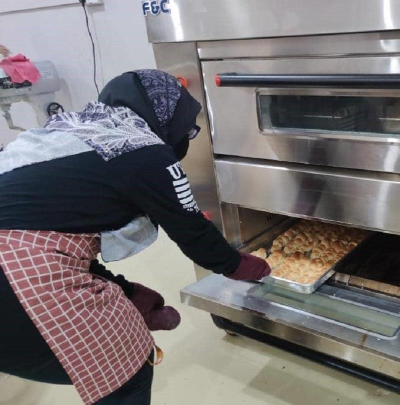 One of Ridzuan's workers taking out a tray of freshly made buns from the oven. ― Picture by Ridzuan Jamal