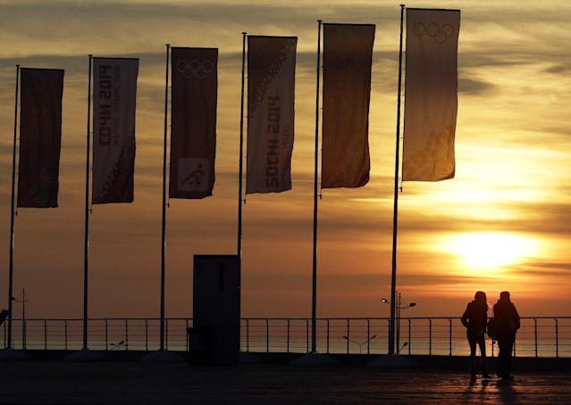 People stand near Olympic flags as they watch the sun set over the Black Sea at the 2014 Winter Olympics, Saturday, Feb. 8, 2014, in Sochi, Russia. (AP Photo/Mark Humphrey)
