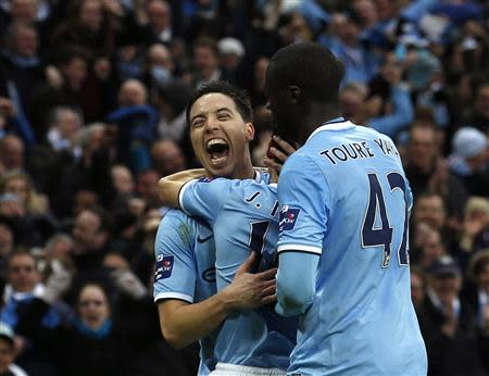 Manchester City's Jesus Navas (obscured) celebrates with team mates Yaya Toure (R) and Samir Nasri (L) after scoring goal against Sunderland during their English League Cup final soccer match at Wembley Stadium in London March 2, 2014. REUTERS/Suzanne Plunkett
