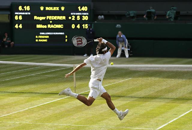 Roger Federer of Switzerland plays a return to go to match point in his game against Milos Raonic of Canada during their men's singles semifinal match at the All England Lawn Tennis Championships at Wimbledon, London, Friday, July, 4, 2014. (AP Photo/Ben Curtis)