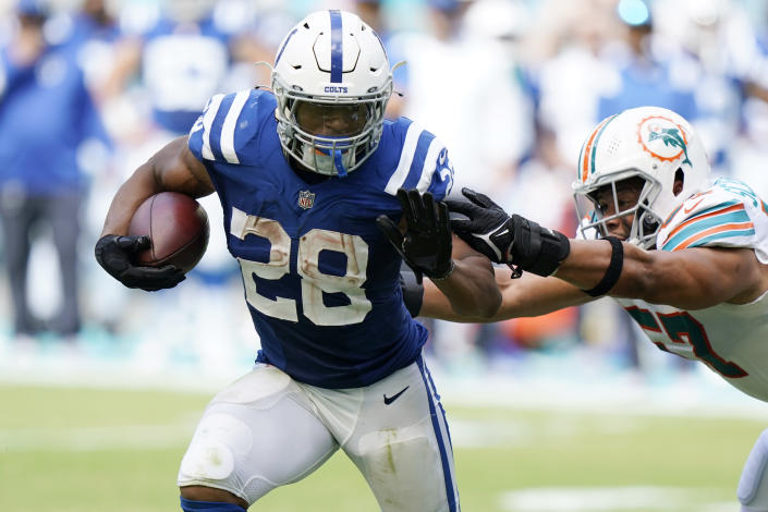 Indianapolis Colts running back Jonathan Taylor (28) avoids a tackle by Miami Dolphins outside linebacker Brennan Scarlett (57), during the second half of an NFL football game, Sunday, Oct. 3, 2021, in Miami Gardens, Fla. (AP Photo/WIlfredo Lee)