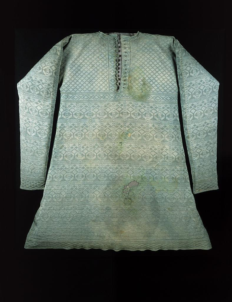 An intricately patterned top that resembles a long sleeved tunic covered in stains and markings