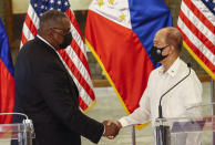 United States Defense Secretary Lloyd Austin, left, and Philippines Defense Secretary Delfin Lorenzana shake hands after a bilateral meeting at Camp Aguinaldo military camp in Quezon City, Metro Manila, Philippines Friday, July 30, 2021. Austin is visiting Manila to hold talks with Philippine officials to boost defense ties and possibly discuss the The Visiting Forces Agreement between the US and Philippines. (Rolex dela Pena/Pool Photo via AP)