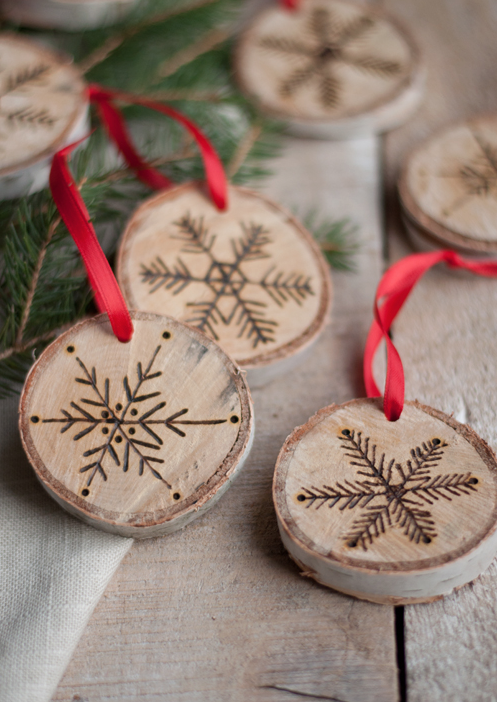 """<p>Using an etching tool, draw a small snowflake onto wood slices. Tie on a red ribbon to complete the look.</p><p><strong>Get the tutorial at <a href=""""http://www.designmom.com/2013/11/the-perfect-gift-etched-snowflake-ornaments-in-birch/#comments"""" rel=""""nofollow noopener"""" target=""""_blank"""" data-ylk=""""slk:Design Mom"""" class=""""link rapid-noclick-resp"""">Design Mom</a>.</strong></p><p><a class=""""link rapid-noclick-resp"""" href=""""https://www.amazon.com/Assorted-Decorations-Ornaments-Super-Outlet/dp/B01FRDI8EY/?tag=syn-yahoo-20&ascsubtag=%5Bartid%7C10050.g.1070%5Bsrc%7Cyahoo-us"""" rel=""""nofollow noopener"""" target=""""_blank"""" data-ylk=""""slk:SHOP WOOD SLICES"""">SHOP WOOD SLICES</a></p>"""
