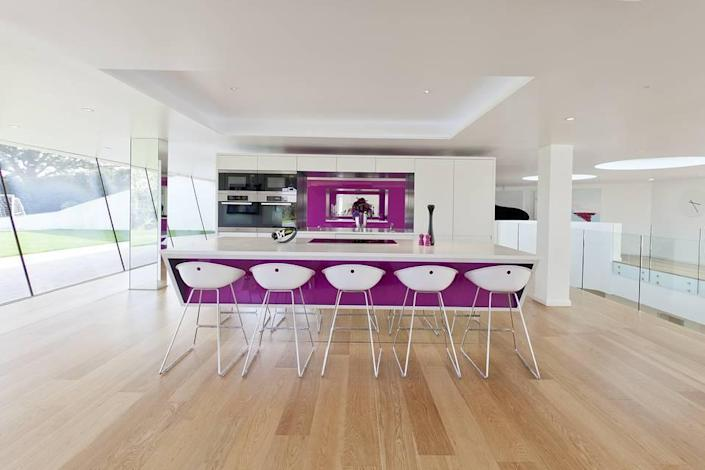 <p>This may be the only super-modern gourmet kitchen we've ever seen that's done in white and magenta. Note the slanting walls of glass at left.</p>