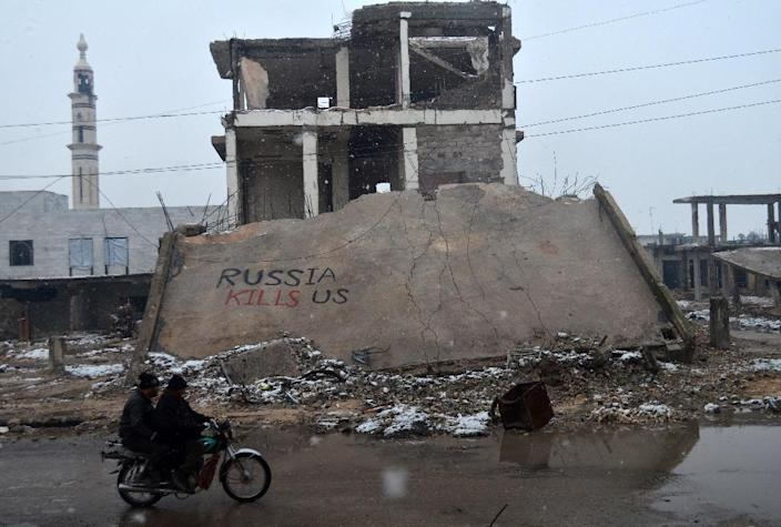 """Syrians ride a motorbike past a collapsed building on which graffiti reads """"Russia kills us"""" in the central Syrian town of Talbisseh in the Homs province on January 1, 2016 (AFP Photo/Mahmoud Taha)"""