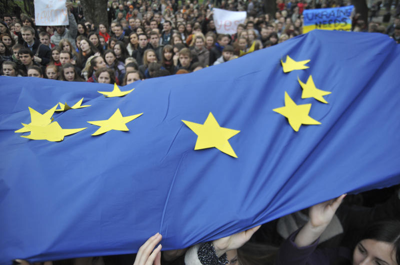 Activists waves European Union flags during a rally in support of Ukraine's integration with the European Union in the center of Lviv, Western Ukraine, Friday, Nov. 22, 2013. Ukraine's Cabinet on Thursday suspended preparations for signing a free trade and a political association agreement with the EU at next week's summit, and the opposition has called on Ukrainians to turn up for a massive anti-government rally to protest the decision. (AP Photo/Pavlo Palamarchuk)