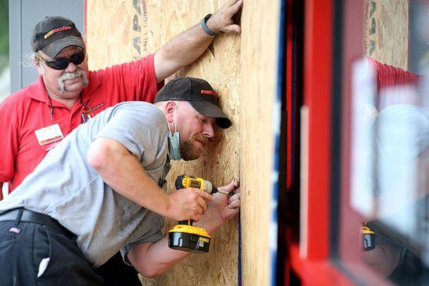 PHOTO:Alex Vidmar, center, and Darrin Manning board up a business as Hurricane Sally approaches in Ocean Springs, Miss., Sept. 14, 2020. (Jonathan Bachman/Reuters)