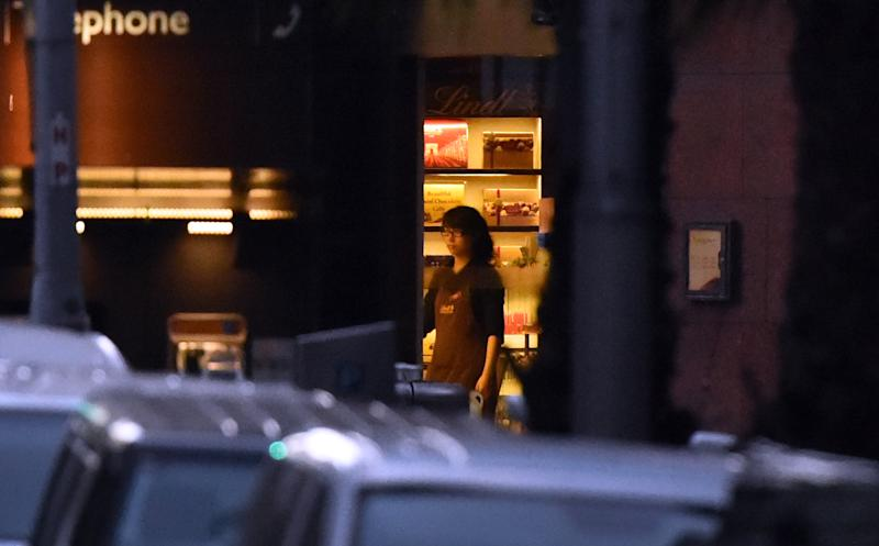 A female hostage stands by the entrance of the Lindt cafe during a hostage siege in Sydney's CBD on December 15, 2014 (AFP Photo/William West)