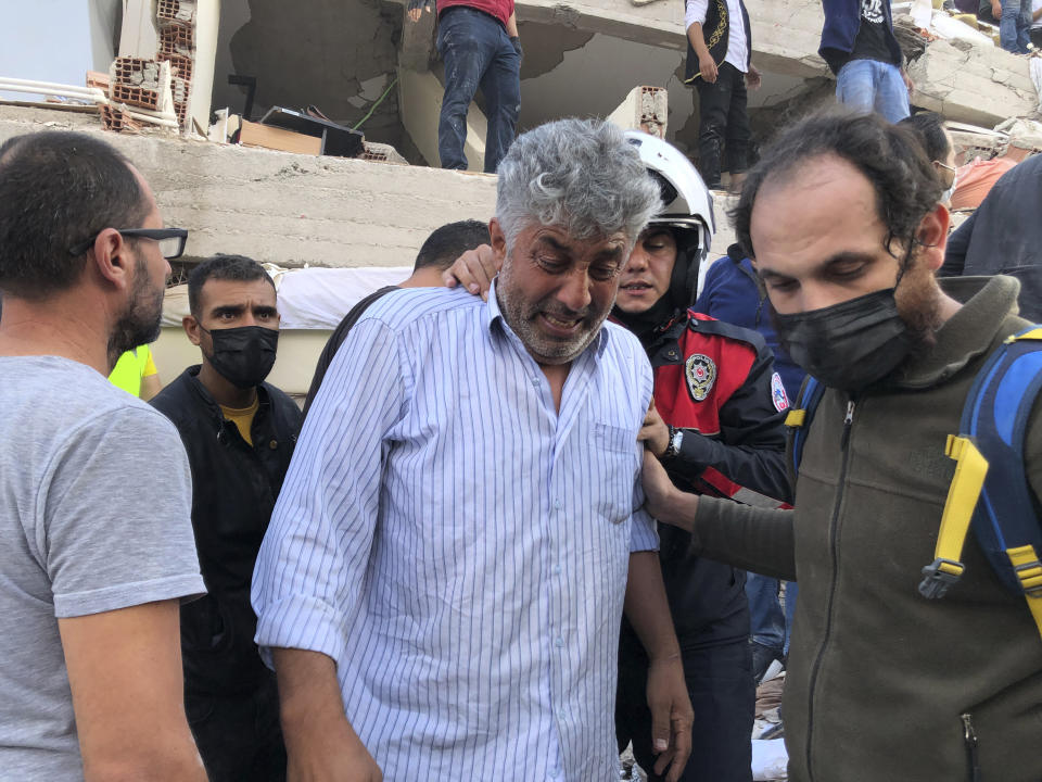 A man weeps as rescue workers and local people try to save residents trapped in the debris of a collapsed building, in Izmir, Turkey, Friday, Oct. 30, 2020, after a strong earthquake in the Aegean Sea has shaken Turkey and Greece. Turkey's Disaster and Emergency Management Presidency said Friday's earthquake was centered in the Aegean at a depth of 16,5 kilometers (10.3 miles) and registered at a 6.6 magnitude.(AP Photo/Ismail Gokmen)