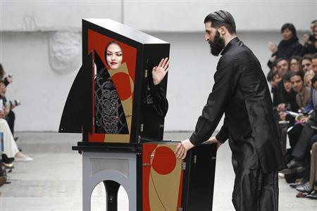 A magician performs with a model who presents a creation by Indian designer Manish Arora as part of his Fall-Winter 2011/2012 women's ready-to-wear fashion collection for French fashion house Guy Laroche during Paris Fashion Week