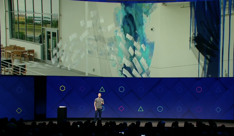 Zuckerberg stands under a slide of a wall with augmented reality graffiti.