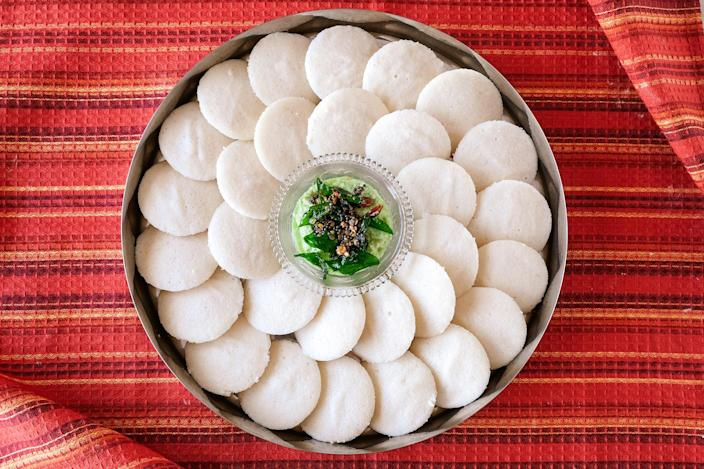 """<p>Idli, steamed cakes made of fermented rice and lentils, are a South Indian staple. These fluffy, soft dumplings are one of my daughter's favorite breakfast foods. She eats them with sambar, a lentil-based vegetable stew. That's one traditional way to serve them, but idli can also be eaten with yogurt, ghee and sugar, or with coconut chutney. This idli recipe is adapted from my former mother-in-law's many emails and texts over the years. As with any fermented foods, making idli is a process. The times suggested in this recipe are just guidelines; use your senses (feel, smell) and your intuition as you work through the recipe. The coconut chutney recipe is adapted from my mother's. Learn more about the story behind this recipe in the article <a href=""""https://www.eatingwell.com/article/7896608/idli-breakfast-comfort-food/"""" rel=""""nofollow noopener"""" target=""""_blank"""" data-ylk=""""slk:These Fluffy Idli with Coconut Chutney Are My Daughter's Favorite Breakfast Comfort Food"""" class=""""link rapid-noclick-resp"""">These Fluffy Idli with Coconut Chutney Are My Daughter's Favorite Breakfast Comfort Food</a>.</p>"""
