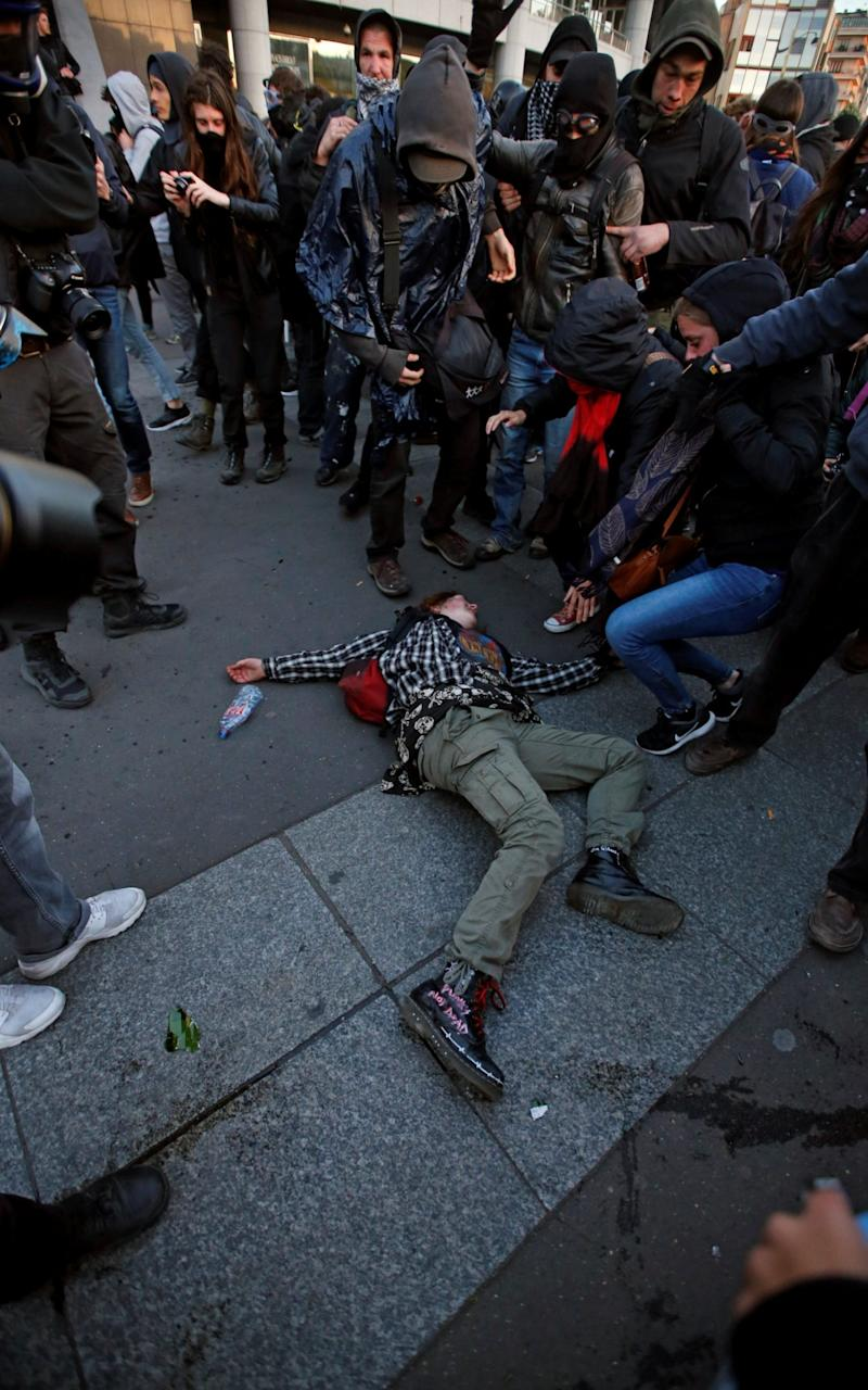 A demonstrator lays on the ground during clashes with police after early results in the first round of 2017 French presidential election, in Paris - Credit:  JEAN-PAUL PELISSIER/REUTERS
