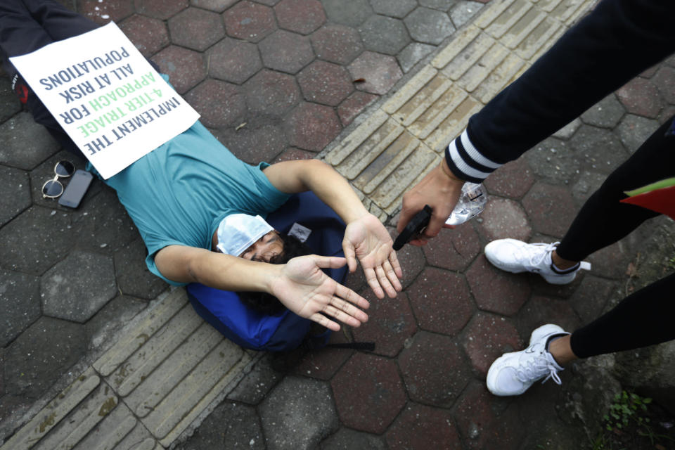 A protester uses a hand sanitizer as he lies on the ground demanding better handling of the COVID-19 pandemic in Kathmandu, Nepal, Saturday, June 20, 2020. Hundreds participated demanding increased testing and protesting alleged corruption by government officials while purchasing equipment and testing kits. (AP Photo/Niranjan Shrestha)