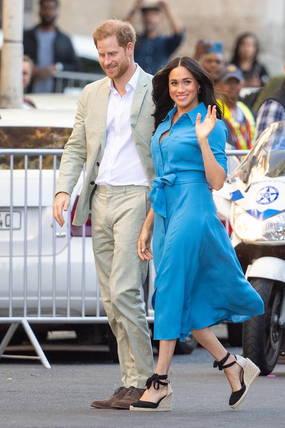 """Meghan wore a £525 belted Veronica Beard shirt dress for her second outfit on day one of the royal tour. It wasn't a new look: the Duchess first wore the dress while visiting Tonga with Prince Harry last year. The dress is sold out in blue, but limited sizes are still available in the red and it's on sale for £210. <a href=""""https://fave.co/2m6h4t2"""" rel=""""nofollow noopener"""" target=""""_blank"""" data-ylk=""""slk:Shop now"""" class=""""link rapid-noclick-resp""""><strong>Shop now</strong></a><strong>.</strong> <em>[Photo: Getty Images]</em>"""