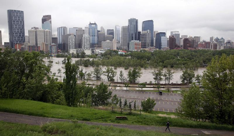 The Bow River overflows in Calgary, Canada on Friday, June 21, 2013. Heavy rains have caused flooding, closed roads, and forced evacuations in Calgary. (AP Photo/The Canadian Press, Jeff McIntosh)