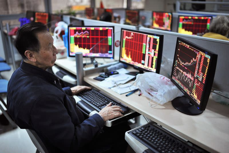 An investor looks at computer screens showing stock information at a brokerage house in Hefei
