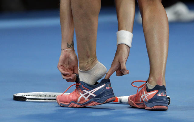 Switzerland's Timea Bacsinszky puts her shoe back on during her third round match against Spain's Garbine Muguruza at the Australian Open tennis championships in Melbourne, Australia, Saturday, Jan. 19, 2019. (AP Photo/Mark Schiefelbein)