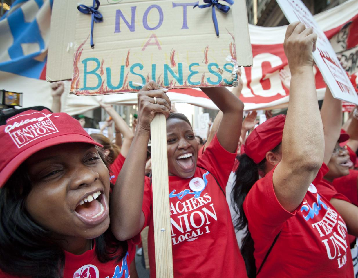 Public school teachers cheer as Chicago Teachers Union President Karen Lewis, unseen, arrives unexpectedly to address a rally of thousands of teachers gathered for the second consecutive day outside the Chicago Board of Education district headquarters on Tuesday, Sept. 11, 2012 in Chicago. Teachers walked off the job Monday for the first time in 25 years over issues that include pay raises, classroom conditions, job security and teacher evaluations. (AP Photo/Sitthixay Ditthavong)