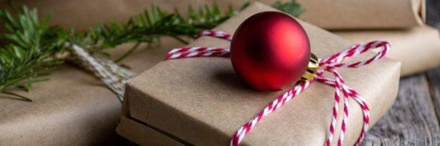 brown paper packages wrapped in red and white string with an ornament on top and garland around