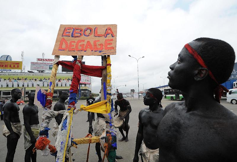 "Members of the artist group ""'Be Kok Spirit'' hold a placard reading ""Ebola, go away"" as they march to raise awareness on the Ebola virus, on August 19, 2014 in Abidjian"