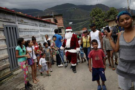 Santa Claus walks during a visit to residents of the slum of Petare in Caracas, Venezuela. REUTERS/Ueslei Marcelino
