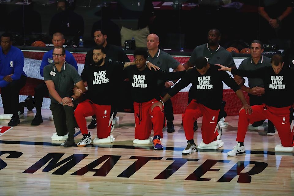 LAKE BUENA VISTA, FLORIDA - SEPTEMBER 09:  Members of the Toronto Raptors kneel during the national anthem before Game Six of the second round of the 2020 NBA Playoffs at ESPN Wide World of Sports Complex on September 9, 2020 in Lake Buena Vista, Florida.  NOTE TO USER: User expressly acknowledges and agrees that, by downloading and or using this photograph, User is consenting to the terms and conditions of the Getty Images License Agreement. (Photo by Kim Klement-Pool/Getty Images)