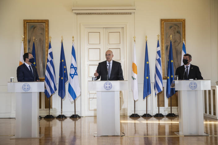 Greek Foreign Minister Nikos Dendias, centre, speaks during a join news conference next to his Israel's counterpart Gabi Ashkenazi, right, and Cypriot Foreign Minister Nikos Christodoulides, left, after their meeting in Athens, on Tuesday, Oct. 27, 2020. (AP Photo/Petros Giannakouris)
