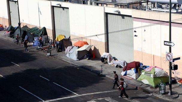 PHOTO: People walk past a homeless tent encampment in Skid Row, Sept. 16, 2019, in Los Angeles. (Mario Tama/Getty Images)