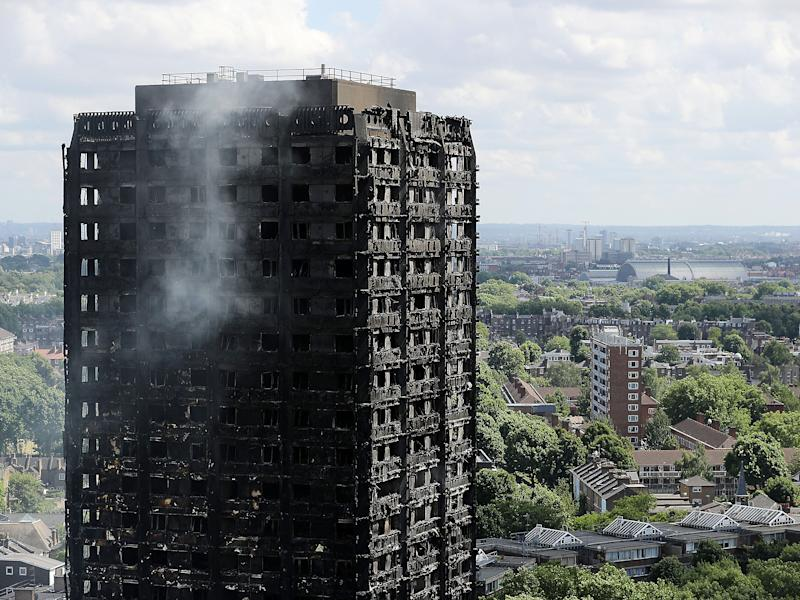Debris hangs from the blackened exterior of Grenfell Tower: Getty