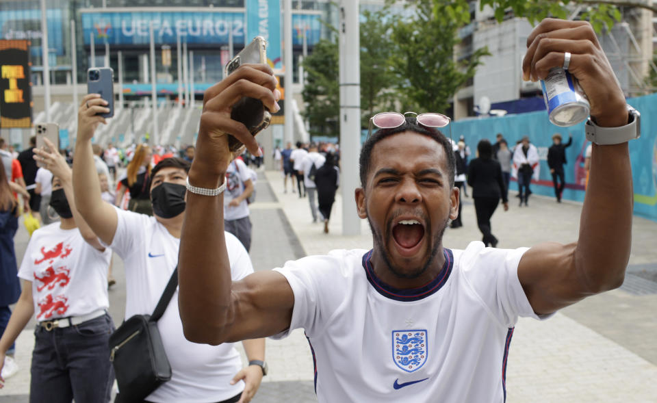 An England fan cheers outside Wembley Stadium in London, Sunday, July 11, 2021, prior to the Euro 2020 soccer championship final match between England and Italy. (AP Photo/David Cliff)