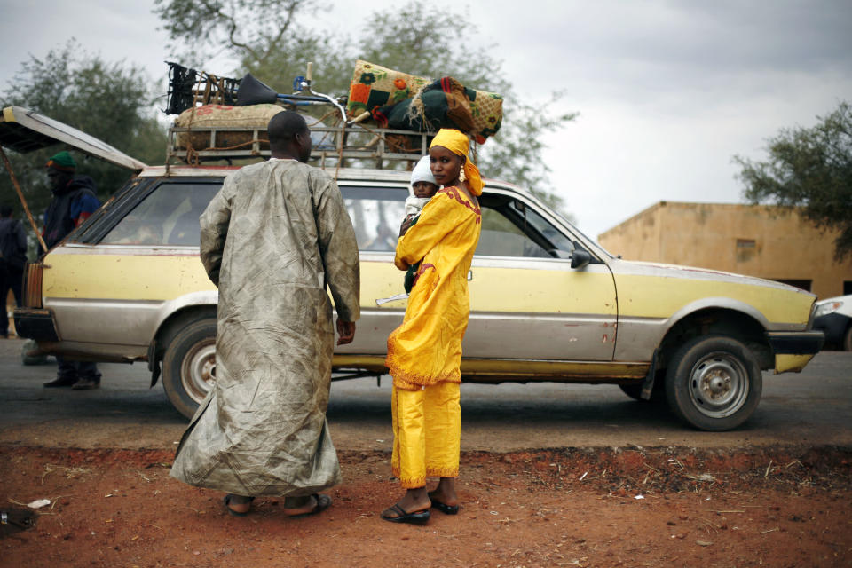 A Malian family's taxi is searched at a checkpoint on the Gao road outside Sevare, some 620 kilometers (385 miles) north of Mali's capital Bamako, Sunday, Jan. 27, 2013. French and Malian troops held a strategic bridge and the airport in the northern town of Gao on Sunday as their force also pressed toward Timbuktu, another stronghold of Islamic extremists in northern Mali, officials said. (AP Photo/Jerome Delay)