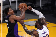 Toronto Raptors guard Kyle Lowry, left, shoots as Los Angeles Lakers forward LeBron James defends during the first half of an NBA basketball game Sunday, May 2, 2021, in Los Angeles. (AP Photo/Mark J. Terrill)