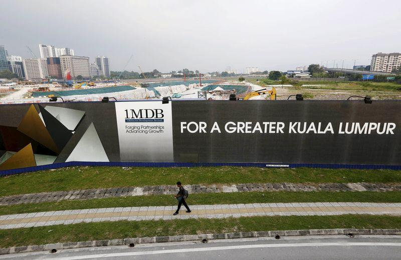 File photo of a man walking past a 1 Malaysia Development Berhad (1MDB) billboard at the funds flagship Tun Razak Exchange development in Kuala Lumpur